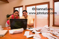 An ethnic couple at home working on their fiances with a laptop computer. Piles of receipts scattered on the table. The couple is smiling and happy.